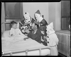 Circus clowns visit sick boy. CC photo Boston Public Library. Image sourced: flashfriday.wordpress.com